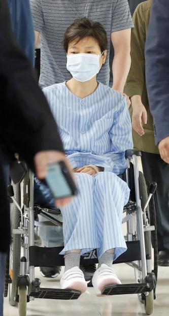 ▲ 환자복을 입은 박근혜 전 대통령이 30일 서울 서초동 서울성모병원에서 허리 통증으로 진료를 받은 뒤 휠체어를 타고 병원을 나서고 있다.