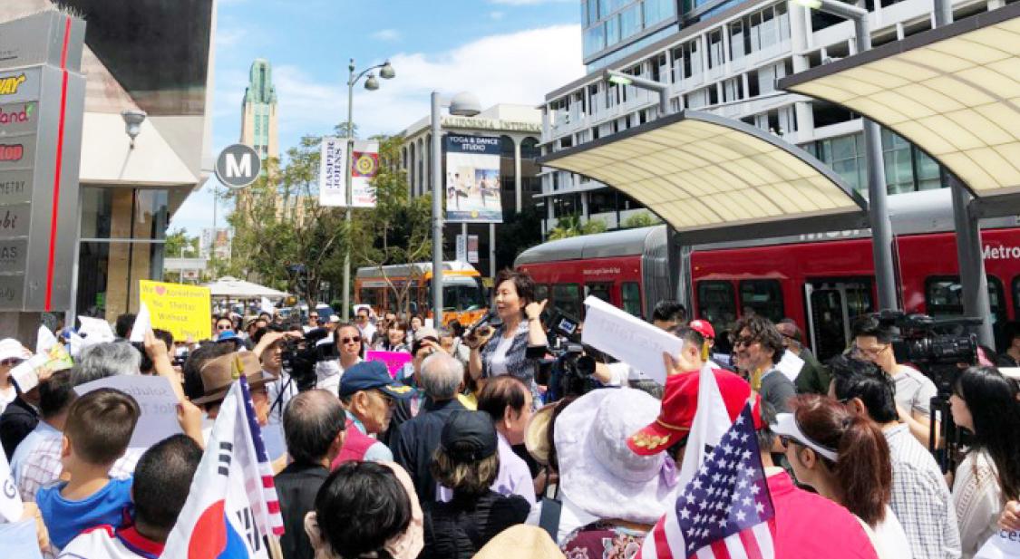 ▲임시 셸터 설치에 분노한 한인들의 6일 시위에 로라전 회장이 입장을 발표하고 있다.