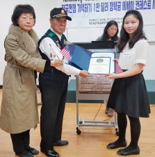 ▲ 중학부 1등상 전하승양(오른쪽)이 장학금을 김해룡 6‧25 유공자회장으로부터 받고 있다.