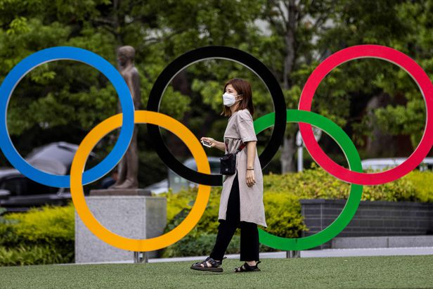 ▲ 도쿄 시내 오륜기 상징물 앞으로 한 시민이 지내고 있다.